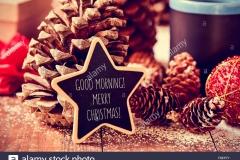 il-testo-buongiorno-buon-natale-scritto-in-una-stella-sulla-lavagna-un-rustico-di-una-superficie-di-legno-con-alcune-pigne-nelle-quali-un-rosso-f8ep7y