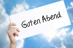 Guten Abend  (Good Evening in German) Sign on white paper. Man Hand Holding Paper with text. Isolated on sky background